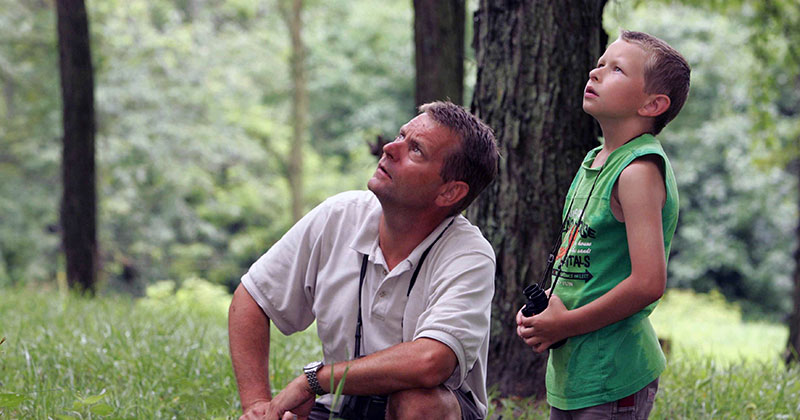 Father and son bird watching in the forest